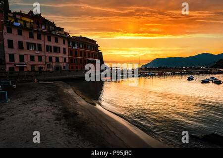 A beautiful golden orange sunset over the small harbor at Vernazza, Italy, part of the Cinque Terre. - Stock Image
