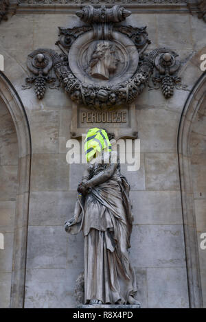 Protesters of Yellow Vests demonstration (Gilets Jaunes) against government, and French President put yellow vest and flag on Paris Opera Garnier - Stock Image