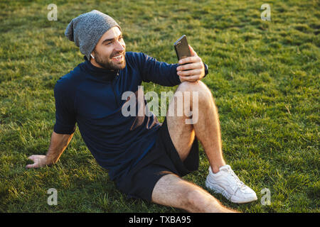 Portrait of smiling sporty man dressed in tracksuit using smartphone and sitting on grass during workout in green park - Stock Image
