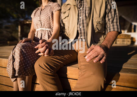 Mid-section of couple sitting on deck on a sunny day - Stock Image