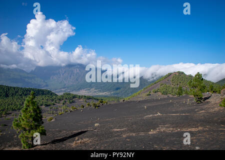 Clouds rolling over the ridge of a volcanic crater at Llanos del Jable, La Palma Island, Canary Islands, Spain - Stock Image