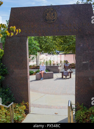 ASHEVILLE, NC, USA-10/17/18: The Veterans Memorial in Pack Square, Asheville, NC, USA, with a young woman sitting beside the sculpture. - Stock Image