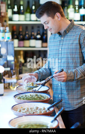 Male Customer In Delicatessen Filling Pot With Green Olives - Stock Image