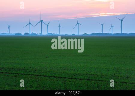 Renewable energy UK, view across a Cambridgeshire fen towards a row of wind turbines, England, UK. - Stock Image