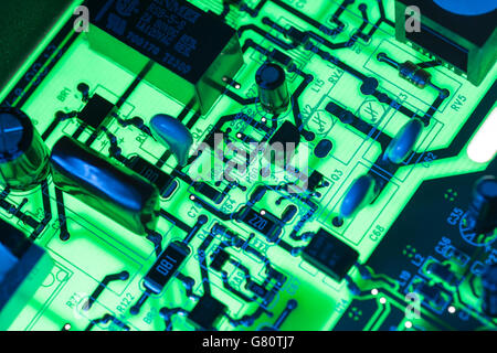 Technology concept - visual metaphor for electronics. Circuit board / pcb showing components lit with blue and green - Stock Image