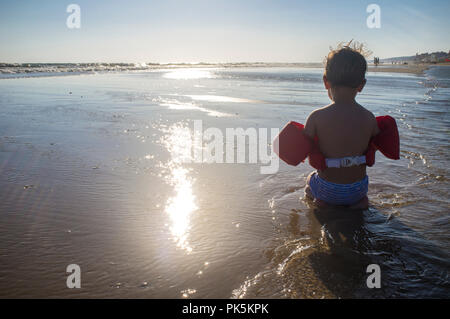 Little boy enjoying on the beach. He wears float life jacket - Stock Image