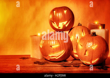 Grunge style photo of a carved pumpkins with scary faces and glowing candles on the table, festive party decoration - Stock Image
