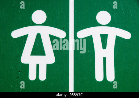 Public restroom toilet WC sign man and woman in green . - Stock Image