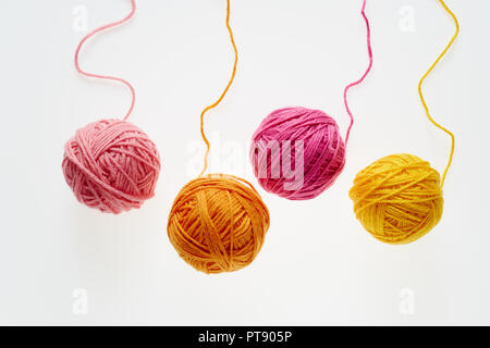 Colorful woolen balls over white background. Balls of wool partially unrolled. - Stock Image