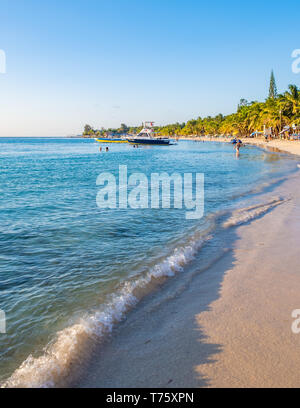 View down West Bay Beach in Roatan Honduras at sunset in portrait orientation. - Stock Image