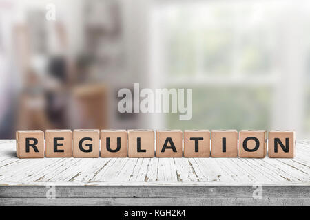 Regulation sign on a wooden table in a bright offive in daylight - Stock Image