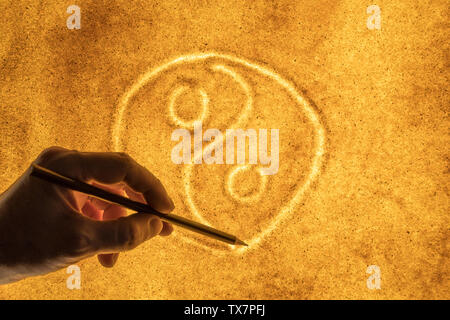 the hands of men draw in the sand a symbol of Yin  Yang. the concept of harmony - Stock Image