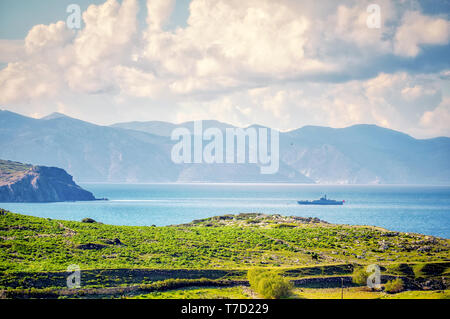 From above view of a meadow field, sea, sky, clouds, mountains and a coast guard assault boat in Gumusluk, Bodrum, Mugla, Turkey - Stock Image