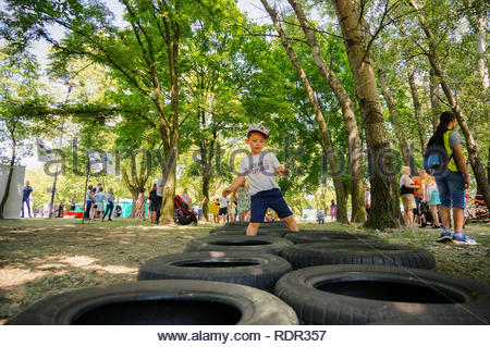 Poznan, Poland - May 27, 2018: Young boy with hat and shorts walking on a tire obstacle at the Kindernalia event on a sunny day - Stock Image