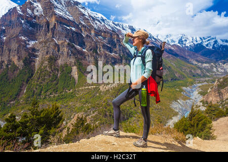 Beautiful Woman Traveler Backpacker Mountains Path.Young Girl Looking Right Way and Take Rest.North Summer Snow - Stock Image