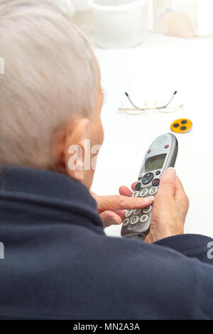 Nearly blind old woman pressing the buttons of a landline telephone especially for seniors with a larger keypad - Stock Image