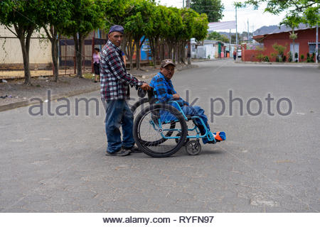 Man pushing another man in a wheel chair.  The man in the chair is old enough to have been in the Contra Wars. - Stock Image