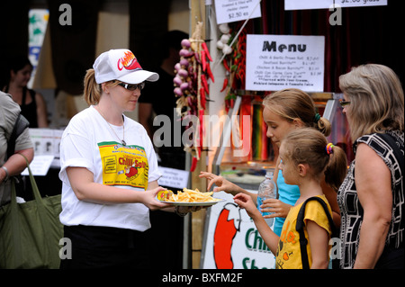 Young woman handing out food samples to woman and two children - Stock Image