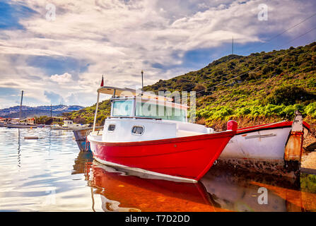 Red and white painted old boats washed upon the shore at Gumusluk bay in Bodrum, Turkey. - Stock Image