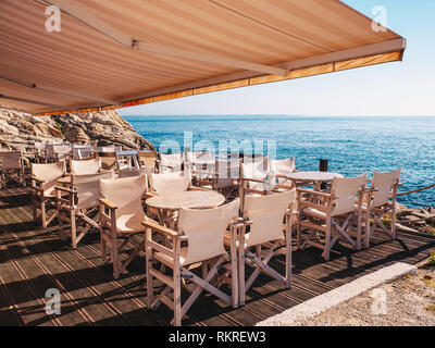 Traditional Greek Tavern near the sea with white wood furniture - Stock Image
