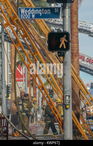 Los Angeles City Fire Department using wood ladders at a commercial building fire. - Stock Image