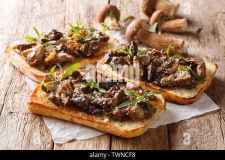 Fresh open sandwiches with fried forest mushrooms, onions, thyme and parmesan cheese closeup on the table. horizontal - Stock Image