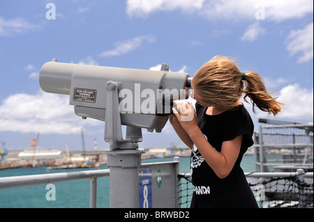 11 year old child looking through coin-operated binoculars. Battleship Missouri, Pearl Harbor, Hawaii - Stock Image
