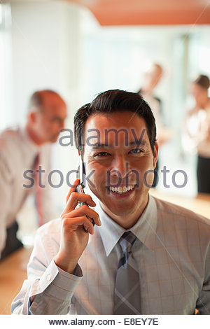 Businessman talking on cell phone in office - Stock Image