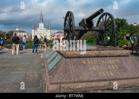 View of an original Louisiana militia cannon sited in the Washington Artillery Park with St Louis Cathedral visible in the distance, New Orleans, USA - Stock Image