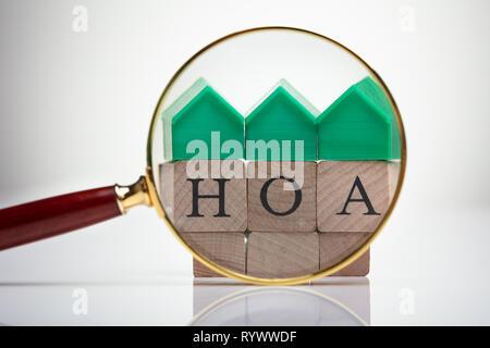 Green House Model Over Homeowner Association Wooden Blocks Seen Through Magnifying Glass - Stock Image
