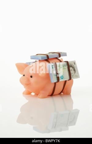 Piggy bank, with saddle of money - Stock Image