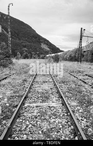 Railroad tracks pointed to the infinite at the abandoned Canfranc International railway station (Canfranc, Pyrenees, Huesca, Aragon,Spain) B&W version - Stock Image