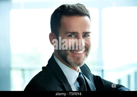 Portrait of smiling businessman standing in hotel lobby - Stock Image
