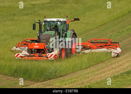 Tractor pulling grass-cutter cutting grass for making hay - Stock Image