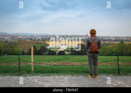 Rear view of a woman wearing a backpack looking at Schloss Schönbrunn Palace and the distant Vienna skyline, Wien, Austria. - Stock Image