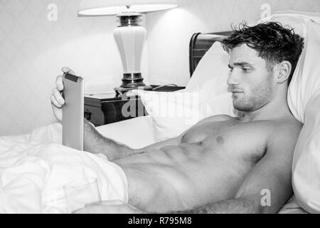 Good looking naked man with six pack abs lying in bed using digital tablet - Stock Image