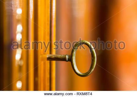 Golden metal key in a wooden cupboard door in soft focus background. - Stock Image
