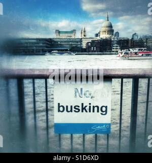 No Busking sign in London, South Bank with St Paul's Cathedral behind - Stock Image