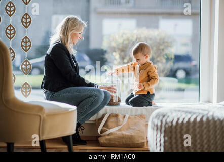 A young woman with a toddler boy resting in zero waste shop. - Stock Image