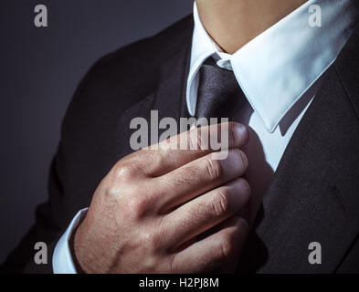 Closeup photo of a man wearing stylish black suit and tie over dark background, body part, mens fashion concept - Stock Image