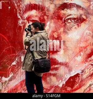 Girl taking photo in graffiti Laneway - Stock Image