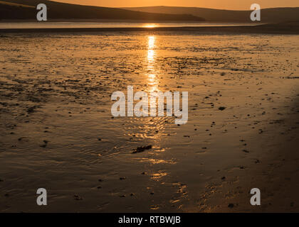 Setting sun over the Camel Estuary, Cornwall UK, at low tide with reflections in the wet sand and shallow water. - Stock Image