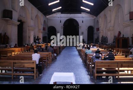 Indigenous Tzutujil attend a Roman Catholic church in San Lucas Tolimán, Lake Atitlan, Guatemala. - Stock Image