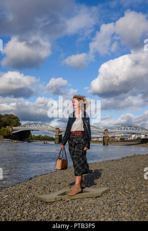 Mature middle aged woman in Autumn fashion clothes by the River Thames at Barnes Mortlake London UK - Stock Image
