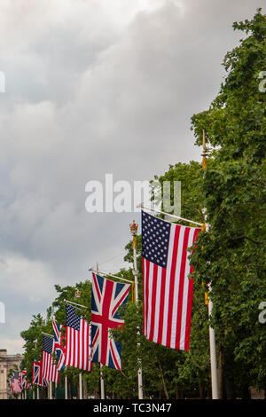 People enjoy the view of Union and American flags on The Mall with Buckingham Palace in the distance - celebrating Donald Trump's visit in June 2019 - Stock Image