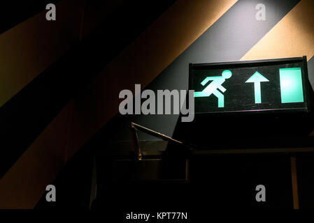 Emergency exit sign in green neon and internal interior light with copyspace area - Stock Image