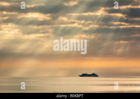 Silhouette of Ferry in Shafts of Morning Light on Dublin Bay in Ireland - Stock Image