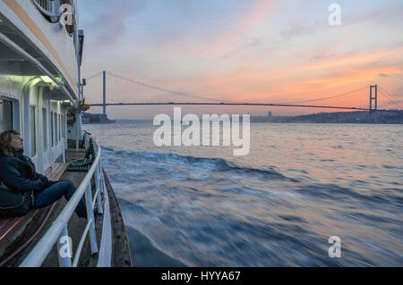 A ferry boat sails along the Bosphorus towards the first Bosphorus bridge and Istanbul city center. - Stock Image