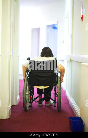 elderly incapacitated lady pushing herself in a wheelchair along a corridor in a government care home - Stock Image