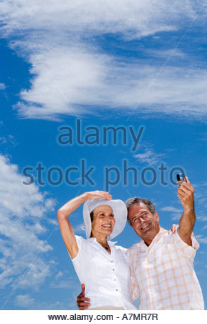 Senior couple standing on beach man taking photograph with camera phone smiling low angle view - Stock Image